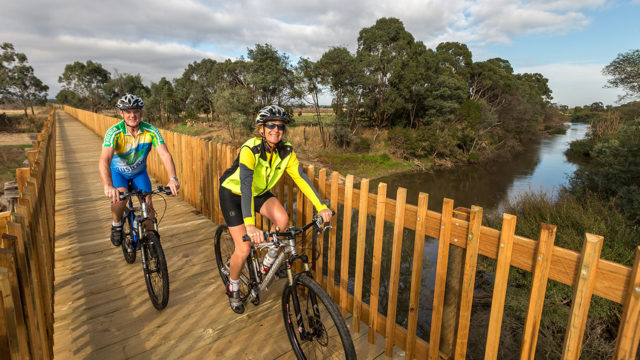 cyclists riding over the bridge on the Gippsland Plains Rail Trail